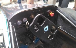 Cockpit del monoplaza eléctrico con el logo del equipo en el volante.